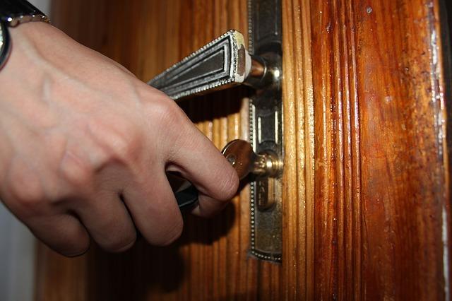 mano de persona con llave abriendo una cerradura de una puerta de apertura de puertas Cádiz