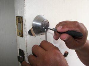 manos con herramientas abriendo una cerradura de una puerta blanca